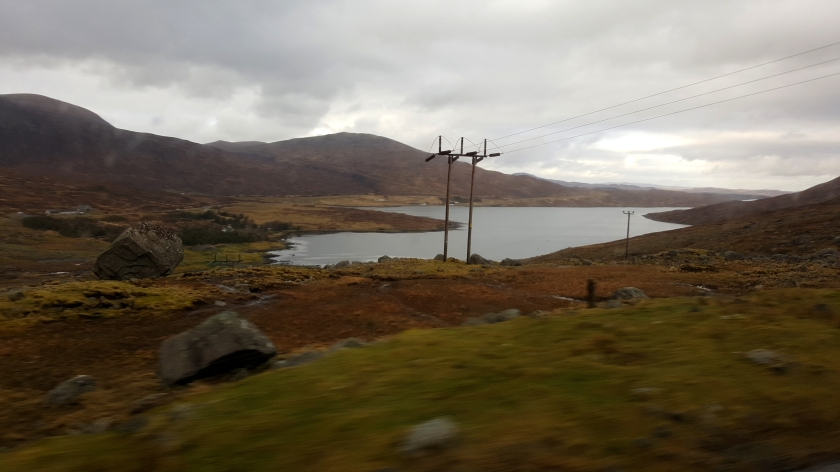 A double electrical pole stands at the edge of a bay in a orange and green hilly landscape