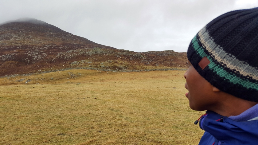 A woman's head turns to face the mist covered peak of a dry brown mountain.