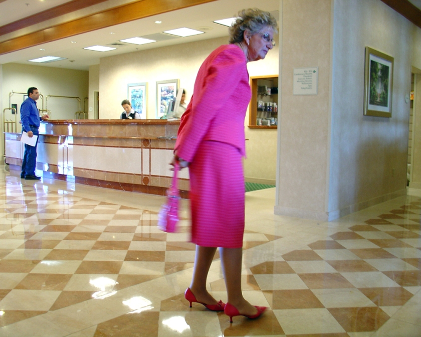 A woman in a bright pink suit in the marble lobby of a hotel