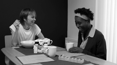 A white woman holding a cigarette shares a laugh with a black woman at the kitchen table.