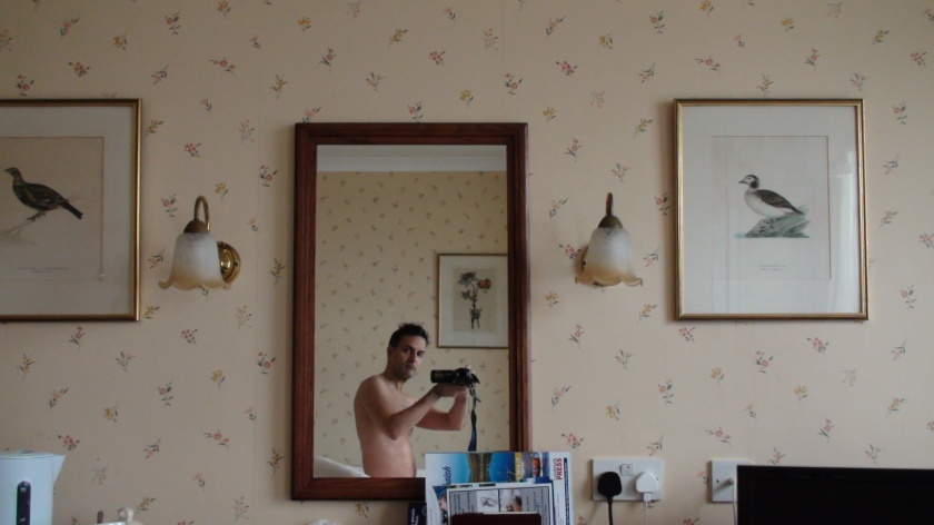 A bare-chested man takes a photo in the mirror of his hotel room