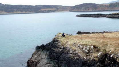 A woman sits on the edge of a rocky cliff jutting into a bay