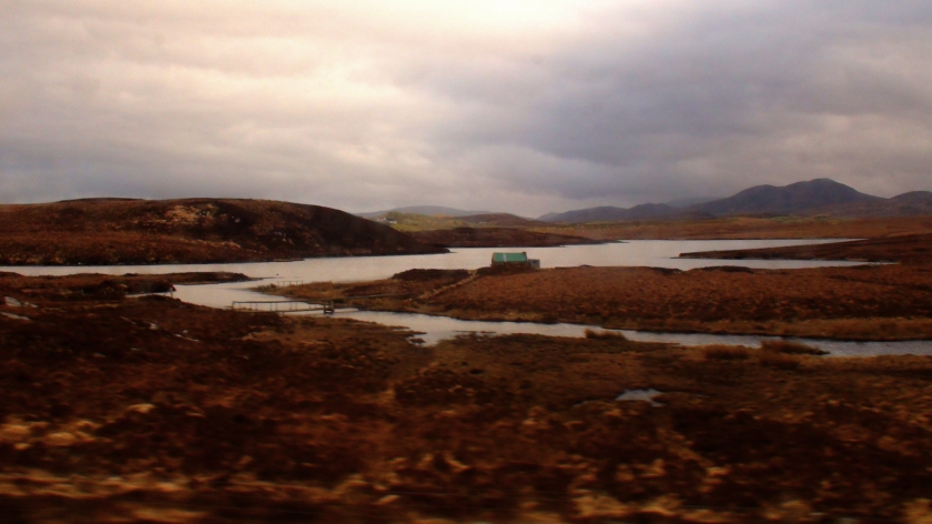 A copper coloured landscape with a winding stream and a tiny house in the background.