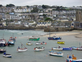 Colourful fishing boats sit on beach in front of a village on a hill