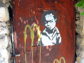 Grafitti of a stencilled child's head tagged with a dropping McDonald's logo