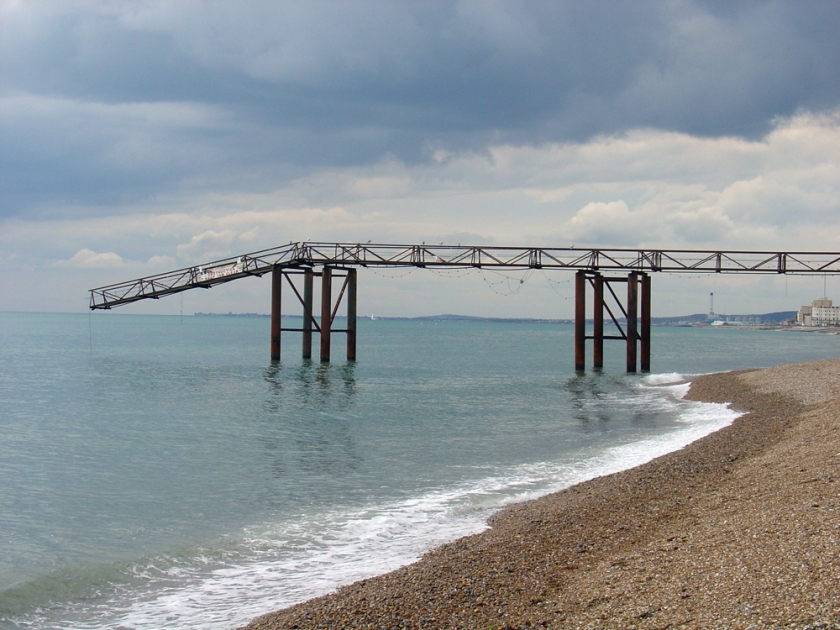 At the edge of the sea the steel of a broken pier droops towards the water