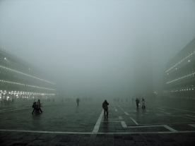 Silhouetted figures in St. Mark's Square in heavy mist