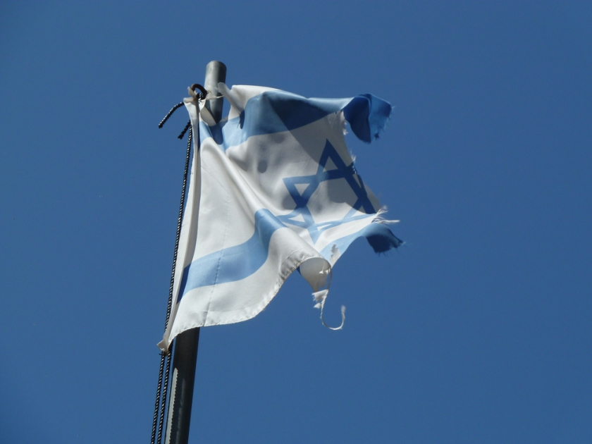 A tporn and ragged Israeli flag ripples against a blue sky