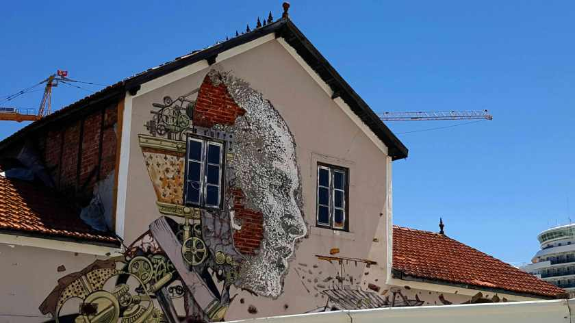 The side a building with a peeling mural showing a man's head composed of machine gears