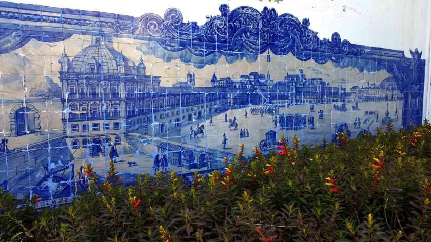 The tile mural in blue and white shows historical Lisbon scene