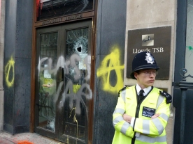 A young policeman in front of a Lloyd's of London entrance whose glass has been smashed and grafittied.
