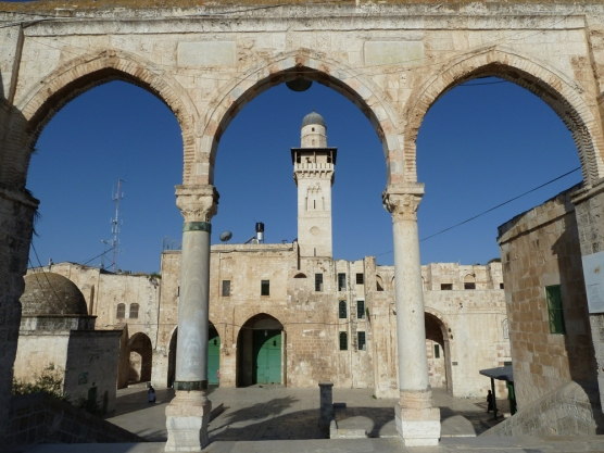 A mosque with minaret seen through ancient arches against a blue sky