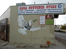 A concrete souvenir shop with a sign a painted mural of a dove wearing a protective vest