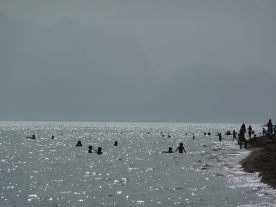 Swimmers silhouetted in the sea on a hazy day