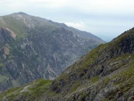 Two mountain peaks, stony grey with green moss