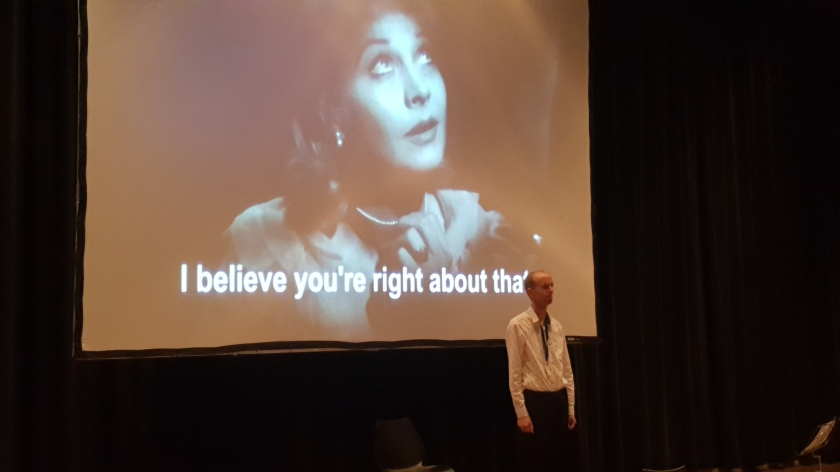 "Tim stands in a white shirt before a projection of Vivien Leigh as Blanche du Bois. The subutitle reads, ""I believe you're right about that."""
