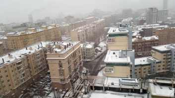 Old apartment blocks seen from above covered in snow