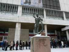 Bronze worker statues stands above a queue of people in the snow