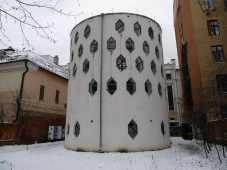 Squat white cylindrical building with rows of jewel shaped windows