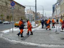 Team of snow shovellers in orange on city street with large buildings