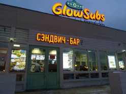 Signage in Roman and Cyrillic for Glow Subs attached to fast food restaurant with people inside