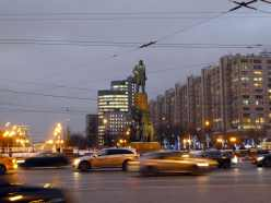 Statue of Lenin stands over busy intersection at dusk