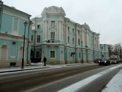 Snow covered street and sidewalk with pedestrian before pastel blue and white Art Nouveau building