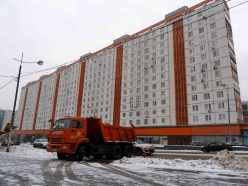 Orange dumptruck before orange and white Soveit era apartment block on snowy street