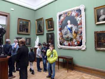Boy standing in front of paintings at State Tretyakov Gallery