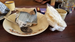a folded newspaper package tied with string sits in a bowl beside a metal spoon, sided with plastic wrapped Indonesian rice cakes