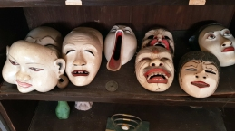 Seven Javanese theatrical masks, carved wood painted white with red and black features, smile, frown, and grimace, with the one at centre's mouth open wide vertically like a baby bird.