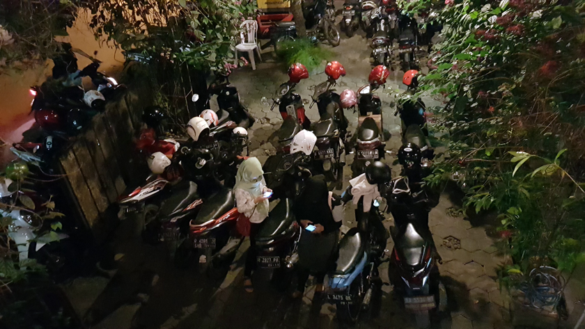 Seen from above, two young woman, one wearing black hijab, the other white, consult their mobile surrounded by motorbikes