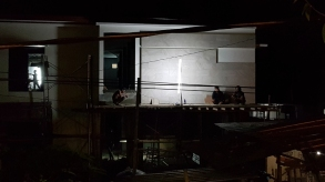 Silhouetted by an electric lamp, figures rest on the balcony of a half constructed house. One squats, consulting his phone.