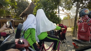 Two women in lime green gymsuits share a bicycle, their heads covered in white hijab and turned away, wedged between motorbikes.