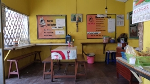 Interior of a warung, a small restaurant with picnic table and benches with the menu in Indonesian on the wall.