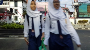 Blurred by their motion, two schoolgirls in uniform, including neckties and hijab, cross the road.