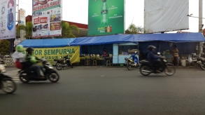 Urban street with food stall beneath giant billboards, at scooters pass in the foreground.