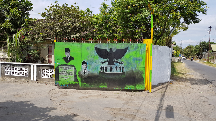 A mural painted on an open gate shows busts of Sukarno and Suharto beside the black silhouette of a spread-winged eagle hovering over a platform of small figures