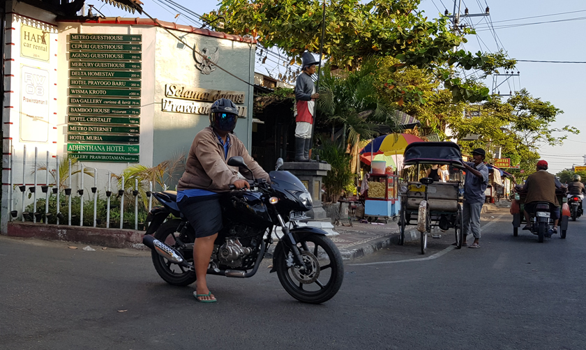 An androgynous motorcyclist wearing an opaque bubble helmet over their face rests in the road beside becak driver adjusting the awning of his vehicle