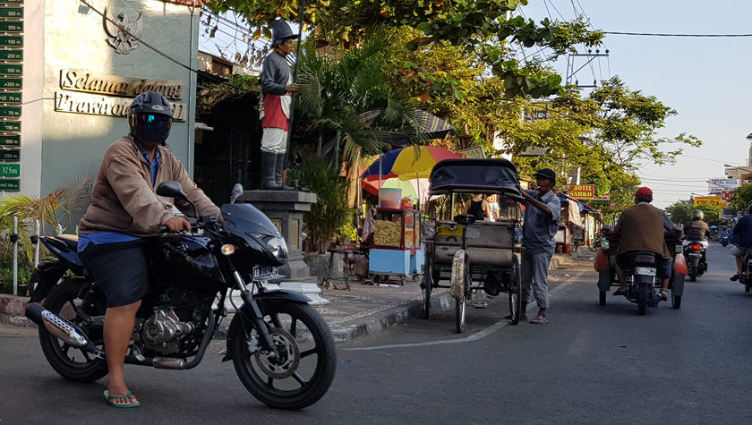 Large motorcyclist rests in the road with opaque bubble helmet beside a becak driver adjusting the awning of his vehicle