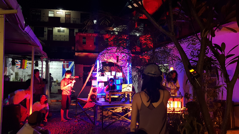 In the courtyard lit by purple and red light, band of electronic musicians and singer perform while one man films and others listen and watch