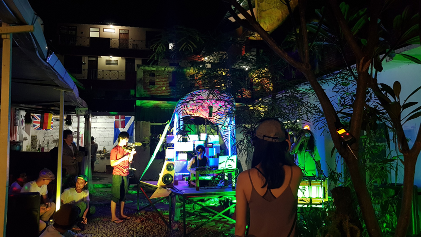 In the courtyard lit by blue and green light, band of electronic musicians and singer perform while one man films and others listen and watch