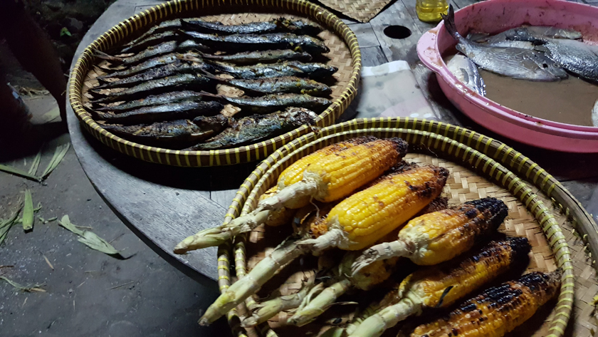 Baskets of grilled and charred corn on the cob and sardines