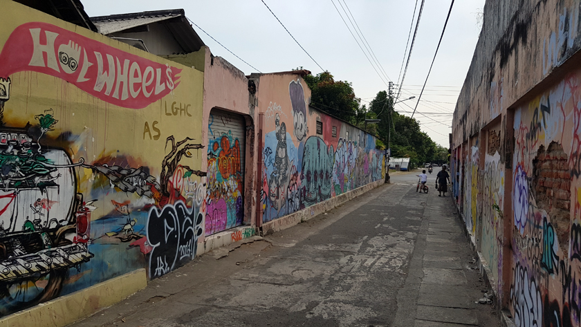 Jogjakarta backstreet, with colourful street art marking concrete walls and, in the distance, an older woman and a child on a bicycle.