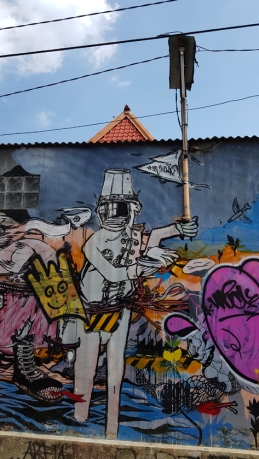 Jogjakarta street art: Surrounded by cartoon figures, a uniformed man with reflective face and steel hat carries a pole that extends into an actual street light.