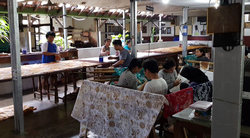 Male and female batik workers paint cloth in a shop