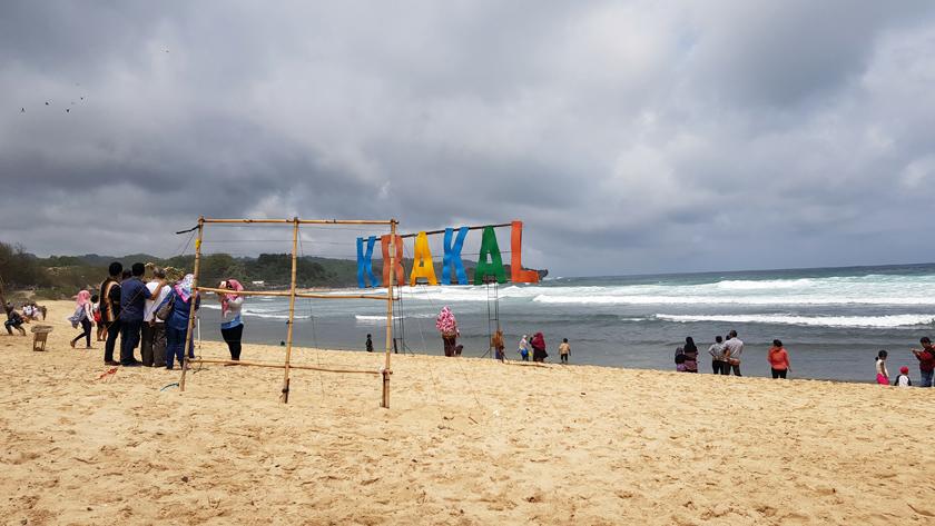 "Seashore with people at water's edge behind a handmade sign reading ""Krakal"""