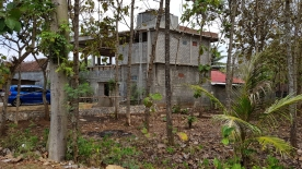 Concrete block house under construction in the middle of a forested landscape