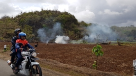 Two people on a motorbike pass a ploughed field with smoke billowing from burning waste