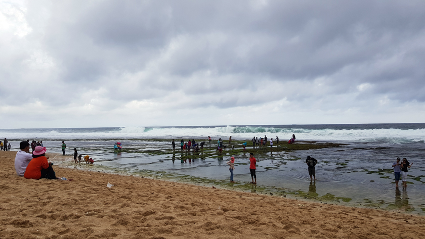 People wade along a seashore as the surf rolls in.